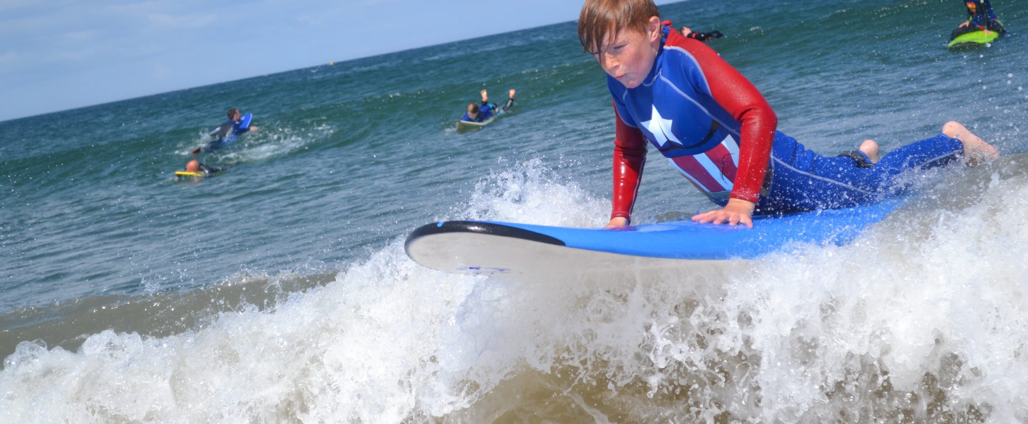 boy dressed as captain america surfing