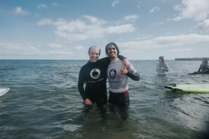 two men arm in arm smiling in sea